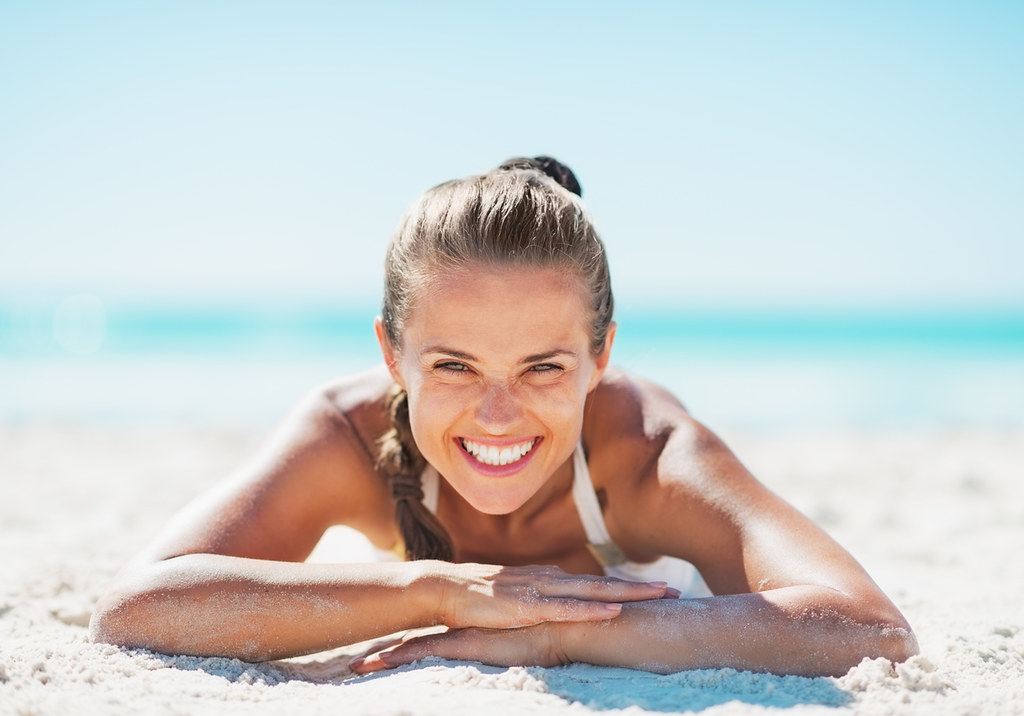 Portrait of smiling young woman in swimsuit laying on sandy beach