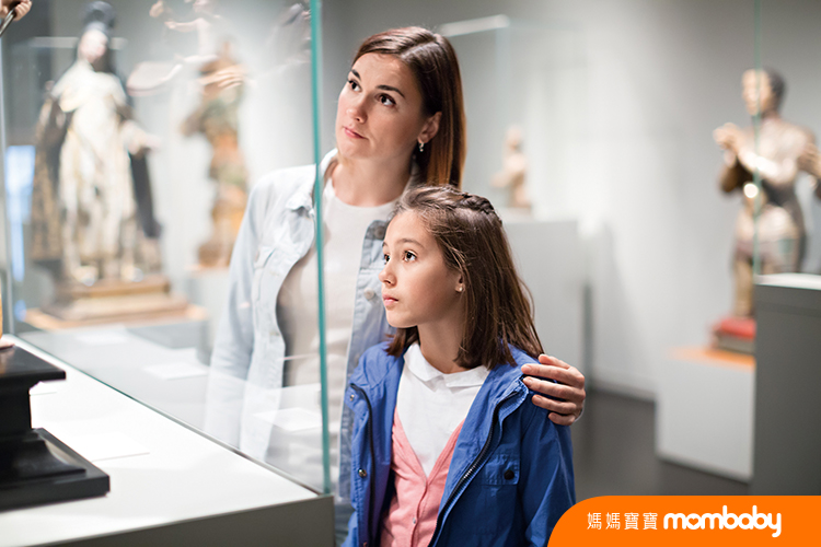 Adult mom and daughter looking at medieval expositions in museum